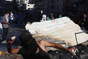 Palestinian protesters clash with Israeli security forces following Friday prayers at Shuafat refugee camp in the West Bank