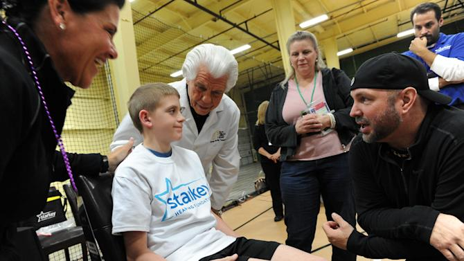 A young boy talks to country music singer Garth Brooks, right, after Starkey Hearing Foundation founder Bill Austin, center, fit him with a hearing aid at The Citi Garth Brooks Super Pro Camp on Friday, Feb. 1, 2013 in New Orleans. (Photo by Cheryl Gerber/Invision for Starkey Hearing Foundation/AP Images)