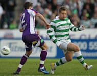 Celtic&#39;s Kris Commons (right) clashes with Perth Glory&#39;s Scott Neville in a friendly game in Perth. Celtic began the defence of their Scottish Premier League title with a narrow 1-0 win over Aberdeen thanks to a late Kris Commons strike at Celtic Park on Saturday