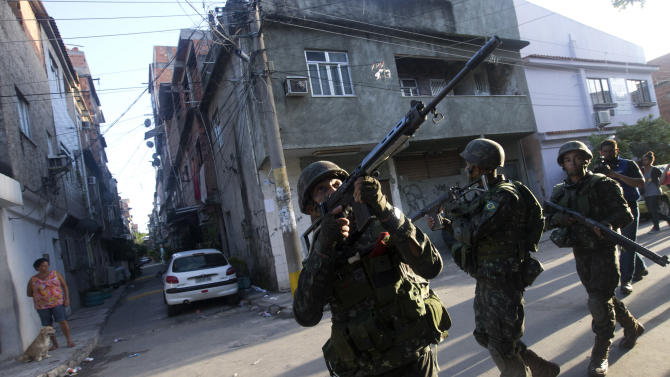 Army soldiers take position during an operation to occupy the Mare slum complex in Rio de Janeiro, Brazil, Saturday, April 5, 2014. More than 2,000 Brazilian Army soldiers moved into the Mare slum complex early Saturday in a bid to improve security and drive out the heavily armed drug gangs that have ruled the sprawling slum for decades. (AP Photo/Silvia Izquierdo)