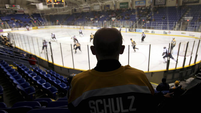 """FILE - In this March 3, 2010, file photo, Johnstown Chiefs fan Robert Schulz watches a minor-league hockey game against the Kalamazoo Wings at the Cambria County War Memorial Arena in Johnstown, Pa. The Chiefs moved to Greenville, S.C., from Johnstown two years ago. A new group of investors are trying once again to support a hockey team to play in this same arena in the gritty western Pennsylvania city whose rich minor-league hockey history produced the cult movie hit """"Slap Shot,"""" this time by relocating a junior league franchise from Alaska. (AP Photo/Carolyn Kaster, File)"""