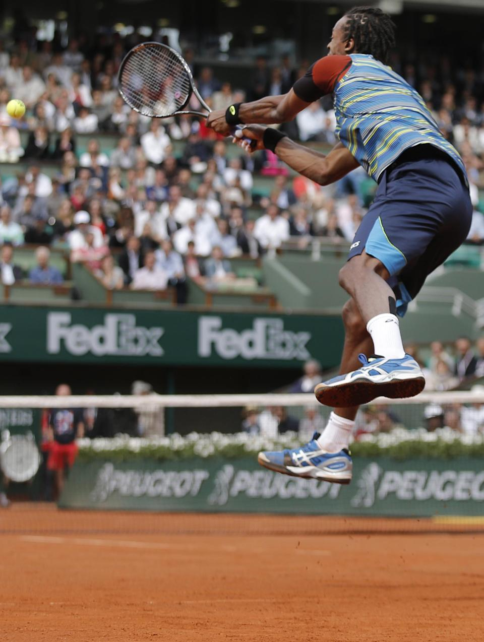 Gael Monfils of France jumps to return against Tomas Berdych of the Czech Republic in their first round match of the French Open tennis tournament, at Roland Garros stadium in Paris, Monday, May 27, 2013. (AP Photo/Christophe Ena)