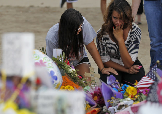 Brittani Roehr, left, from Wichita, Kan., and Chelsea Holi, from Aurora, react at the memorial across from the movie theater, Sunday, July 29, 2012 in Aurora, Colo., where twelve people were killed and more than 50 wounded in a shooting attack on July 20. (AP Photo/Alex Brandon) (AP Photo/Alex Brandon)