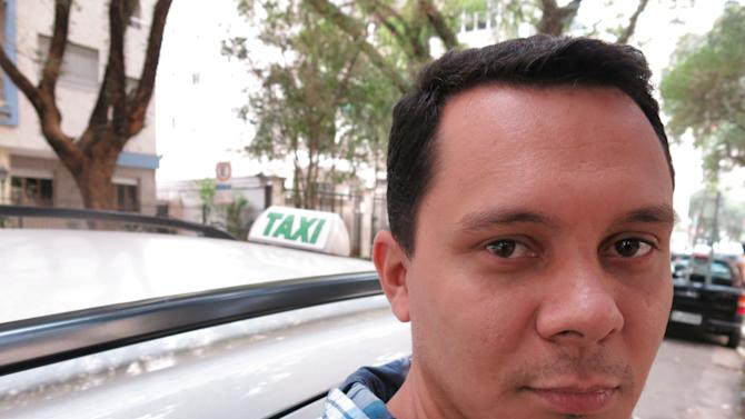 "Taxi driver Iron Pereira e Silva poses for a photo by his cab in Sao Paulo, Brazil, Friday, June 21, 2013. The 35-year-old driver says ""People are taking advantage of this situation to loot and vandalize. The police have responded in the only way they can when faced with such violence."" (AP Photo/Bradley Brooks)"