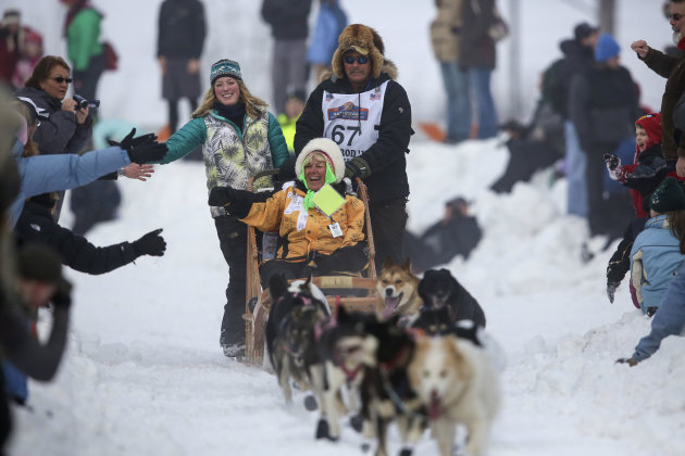 Sonny Lindner's team races down Cordova Street, greeting spectators as they go, during the ceremonial start to the Iditarod dog sled race in downtown Anchorage. The race officially started the day aft