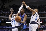 Dallas Mavericks' Brendan Haywood (33) and Shawn Marion (0) defend against a shot attempt by Oklahoma City Thunder's Kevin Durant, center, in the first half of Game 3 in a first-round NBA basketball playoff series, Thursday, May 3, 2012, in Dallas. (AP Photo/Tony Gutierrez)