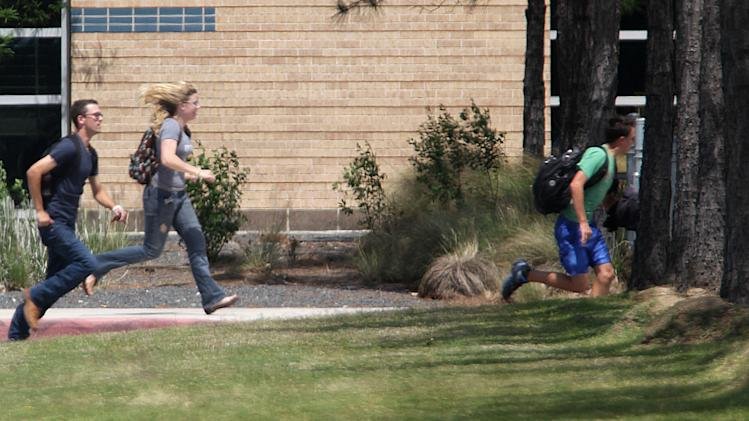 Students run from the Lone Star College's Cy-Fair campus in Cypress, Texas, where a student went on a building-to-building stabbing attack Tuesday, April 9, 2013. The attacker wounded at least 14 people before being subdued and arrested, authorities said.  (AP Photo/Houston Chronicle, James Nielsen) MANDATORY CREDIT
