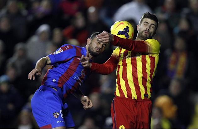 Barcelona's Gerard Pique, right, duels for the ball with Levante's Vyntra from Czech Republic during their La Liga soccer match at the Ciutat de Valencia stadium in Valencia, Spain, Sunday, Ja