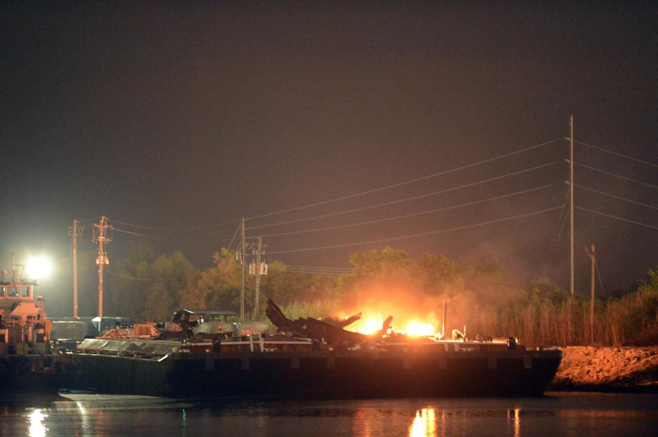 Fire burns aboard two fuel barges along the Mobile River after explosions sent three workers to the hospital Wednesday April 24, 2013. Fire officials have pulled units back from fighting the fire due to the explosions and no immediate threat to lives. (AP Photo John David Mercer)