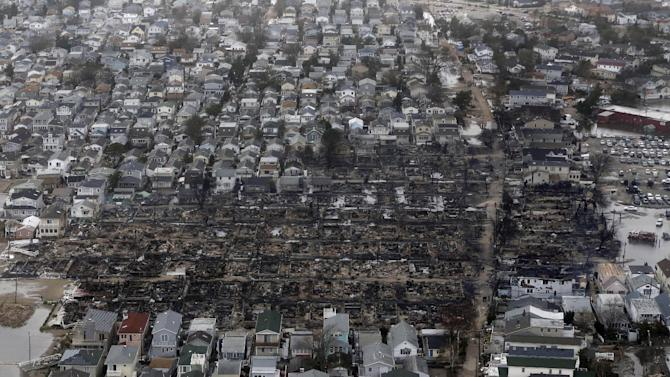 This aerial photo shows burned-out homes in the Breezy Point section of the Queens borough New York after a fire on Tuesday, Oct. 30, 2012. The tiny beachfront neighborhood told to evacuate before Sandy hit New York burned down as it was inundated by floodwaters, transforming a quaint corner of the Rockaways into a smoke-filled debris field. (AP Photo/Mike Groll)