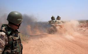 Syrian government forces drive a tank on a road in…