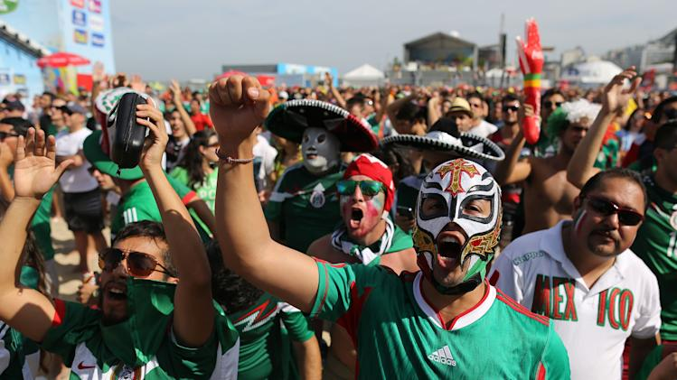 Mexico soccer fans react as they watch their team's World Cup round of 16 match against Netherlands on a live telecast inside the FIFA Fan Fest area on Copacabana beach in Rio de Janeiro, Brazil, Sunday, June 29, 2014. (AP Photo/Leo Correa)