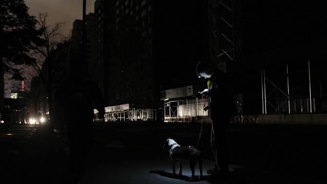 Katie Lynch stands on the street with her dog Merlin in the West Village as she checks her email and voicemail on her iPhone Wednesday Oct. 31, 2012 in New York. Lynch, who lives on West 10th Street and Bleecker Street, said she had no power, cell phone service or internet service, so she needed to go out to check her email and voicemail. (AP Photo/Tina Fineberg)