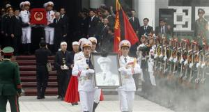 Soldiers hold up the portrait of the late General Vo Nguyen Giap as his coffin is carried during his funeral at the National Funeral House in Hanoi