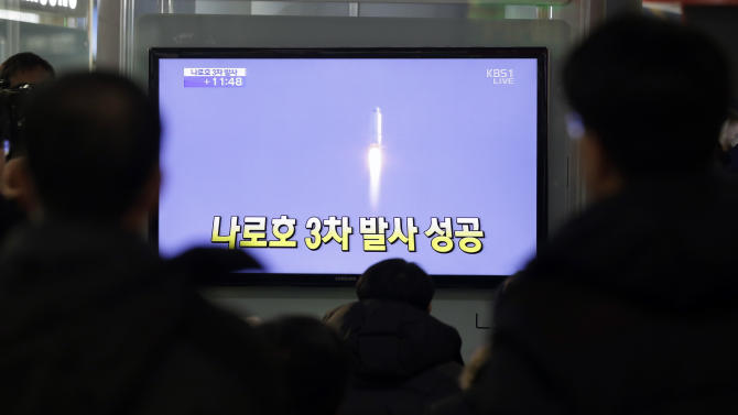 """South Koreans watch a television broadcast reporting the country's first rocket launch at Seoul Railway Station in Seoul, South Korea, Wednesday, Jan. 30, 2013. South Korea has launched a rocket in its third attempt to place a satellite in space from its own soil. The writing reads """" Success third attempt."""" (AP Photo/Lee Jin-man)"""