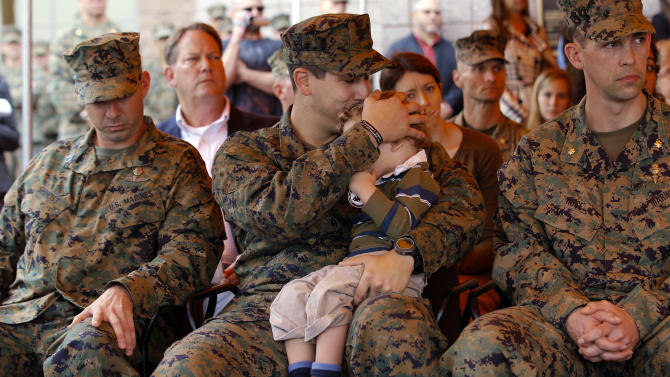 U.S. Navy Petty Officer 2nd Class Patrick Quill, center, kisses his 2-year-old son, Zack, while waiting to receive the Silver Star medal with two other recipients, U.S. Marine Sgt. Frankie Shinost, left, and U.S. Marine Maj. James Rose, right, during a ceremony held at Camp Pendleton, Calif., Monday, Dec. 3, 2012. The three received the medals for their heroism while serving in Afghanistan. (AP Photo/Jae C. Hong)