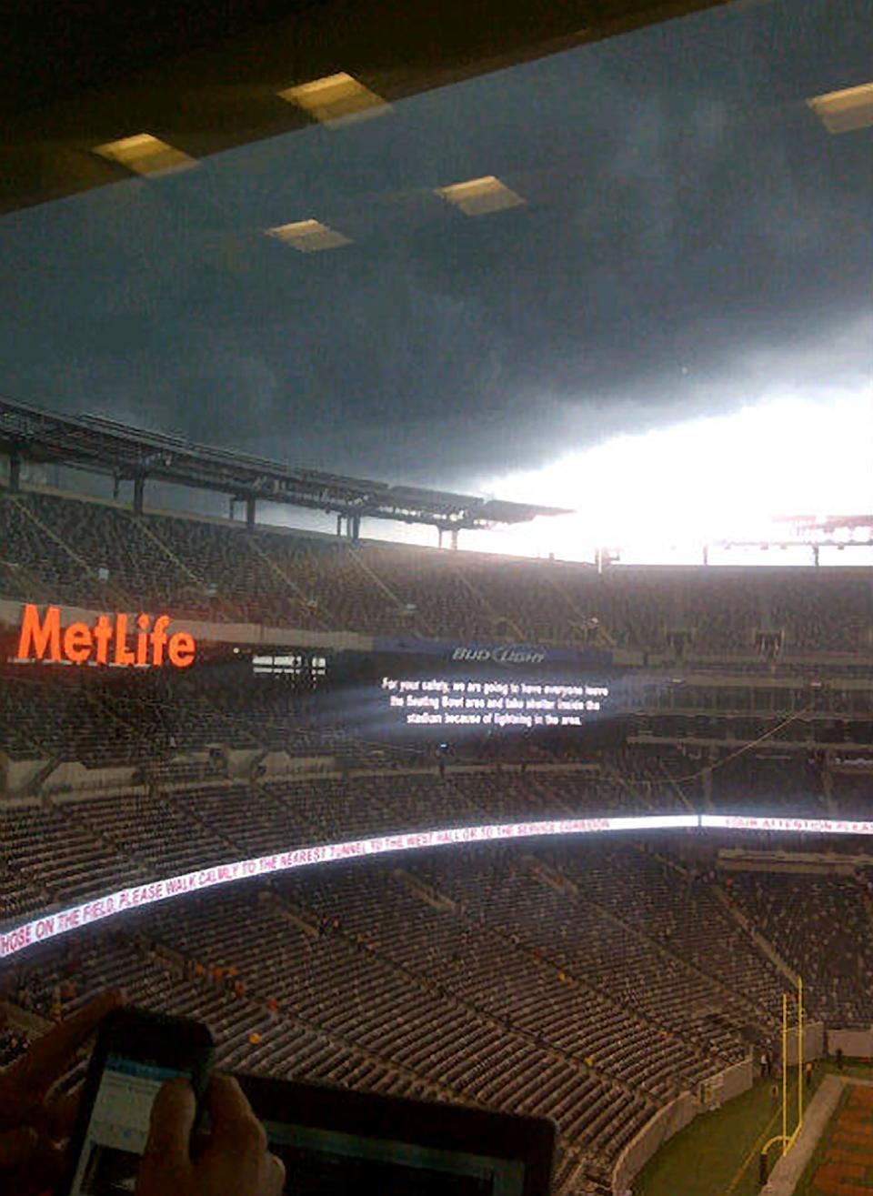 Storm clouds loom over MetLife Stadium, Saturday, Sept. 8, 2012, in East Rutherford, N.J., during an NCAA college football game between Southern California and Syracuse. Because of the hard rain and winds, the game was halted for more than an hour. (AP Photo/Ralph D. Russo)
