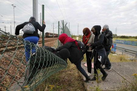 Migrants make their way across a fence near train tracks as they attempt to access the Channel Tunnel in Frethun, near Calais
