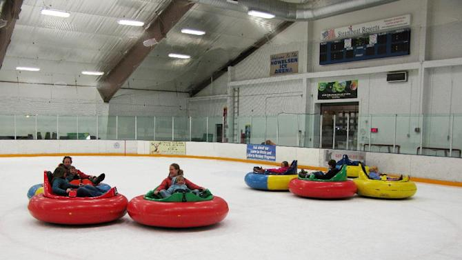 This Dec. 26, 2012 photo shows bumper cars on ice at Howelsen Ice Arena in Steamboat Springs, Colo. The activity is one of a number of relatively new diversions being offered in winter recreation destinations, along with airboarding, snow bikes and snowkiting. (AP Photo/Karen Schwartz)