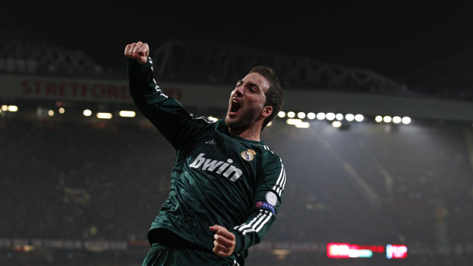 Real Madrid's Gonzalo Higuain from Argentina celebrates after his cross was turned in by Cristiano Ronaldo from Portugal to give his team the lead during their Champions League round of 16 soccer match at Old Trafford Stadium, Manchester, England, Tuesday, March 5, 2013. (AP Photo/Jon Super)