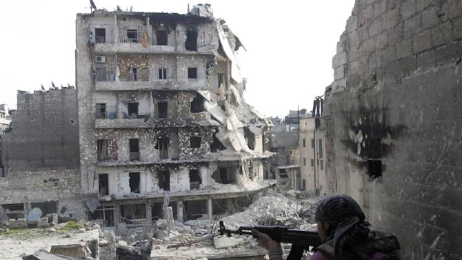 In this photo taken on Thursday, Nov. 29, 2012, a Free Syrian Army fighter is in position in front of destroyed buildings in Aleppo, Syria. Syrian rebels battled regime troops south of Damascus on Friday and Internet and most telephone lines were cut for a second day, but the government reopened the road to the capital's airport in a sign the fighting could be calming, activists said. (AP Photo)