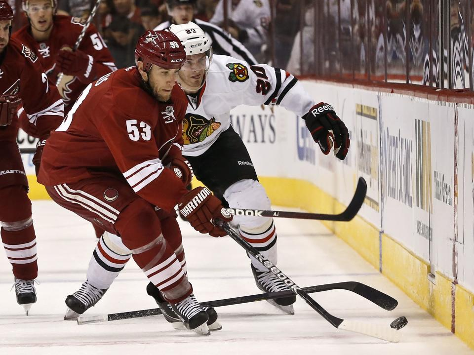 Phoenix Coyotes' Derek Morris (53) gets the puck as Chicago Blackhawks' Brandon Saad (20) loses his stick during the first period in an NHL hockey game Thursday, Feb. 7, 2013, in Glendale, Ariz.(AP Photo/Ross D. Franklin)