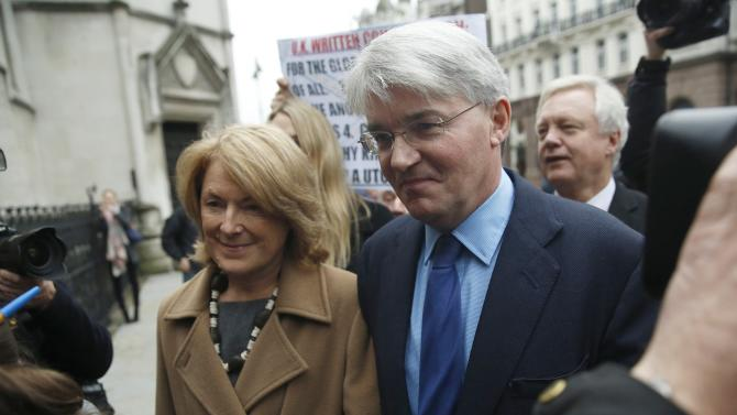 Mitchell, Britain's former Conservative Party chief whip, arrives at the Royal Courts of Justice with his wife Bennett in London