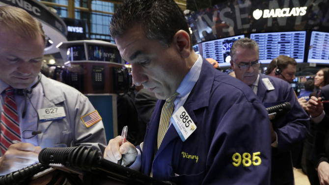 Vincent Quinones, center, works with fellow traders on the floor of the New York Stock Exchange, Friday, April 12, 2013. The stock market is heading lower in early trading after a four-day rise as bank shares weaken. (AP Photo/Richard Drew)