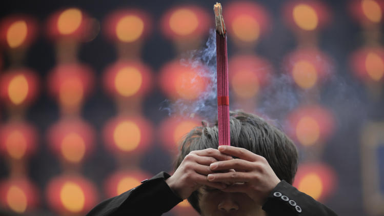 A man burns joss sticks while praying at a temple in Shanghai, China on Monday Feb. 11, 2013, on the second day of the Chinese Lunar New Year. Chinese celebrate the arrival of the Year of the Snake, according to the Chinese Zodiac. (AP Photo/Eugene Hoshiko)