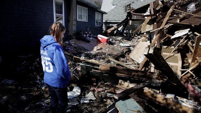 Kate Traina, 14, looks over the rumble of her grandparents house in Staten Island, N.Y., Friday, Nov. 2, 2012.  Mayor Michael Bloomberg has come under fire for pressing ahead with the New York City Marathon. Some New Yorkers say holding the 26.2-mile race would be insensitive and divert police and other important resources when many are still suffering from Superstorm Sandy. The course runs from the Verrazano-Narrows Bridge on hard-hit Staten Island to Central Park, sending runners through all five boroughs. The course will not be changed, since there was little damage along the route.  (AP Photo/Seth Wenig)