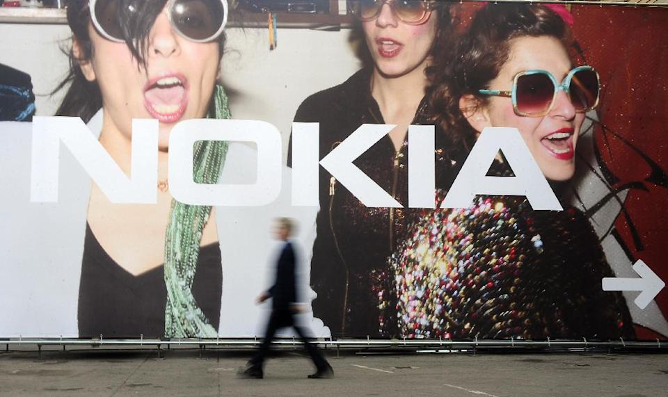 A man walks past a banner of Nokia at the Mobile World Congress, the world's largest mobile phone trade show, in Barcelona, Spain, Tuesday, Feb. 28, 2012. (AP Photo/Manu Fernandez)