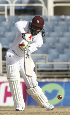 West Indies opening batsman Chris Gayle, right, plays a shot during the second day of their first cricket Test match against New Zealand in Kingston, Jamaica, Monday, June 9, 2014. (AP Photo/Arnulfo Franco)