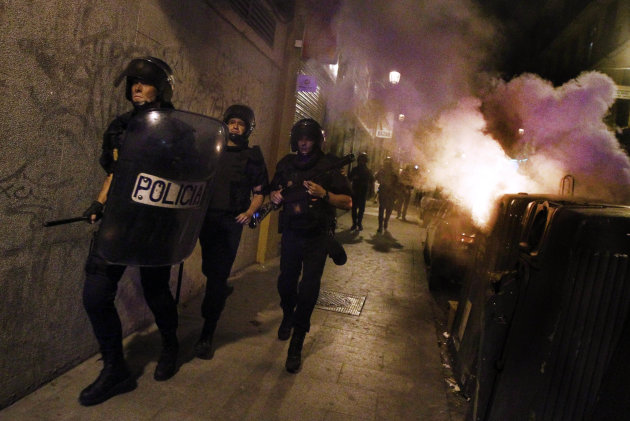 Police riots run after demonstrators protest against austerity measures announced by the Spanish government in Madrid, Spain, Thursday July 19, 2012. Concerns over Spain's attempts to restore market confidence in its economy resurfaced Thursday after a bond auction went poorly and its borrowing costs edged higher - even as the country's Parliament passed the latest round of harsh austerity measures designed to cut its bloated deficit. (AP Photo/Andres Kudacki)