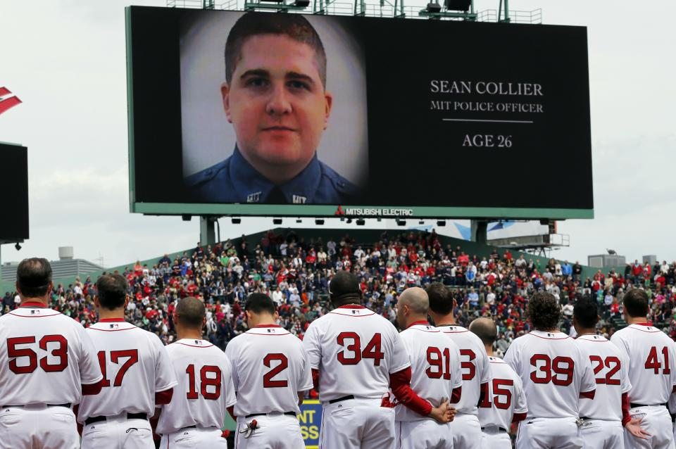 The Boston Red Sox line up during a tribute to victims of the Boston Marathon bombing and its aftermath, as an image of Massachusetts Institute of Technology Police Officer Sean Collier is displayed on the scoreboard, before a baseball game against the Kansas City Royals in Boston, Saturday, April 20, 2013. (AP Photo/Michael Dwyer)