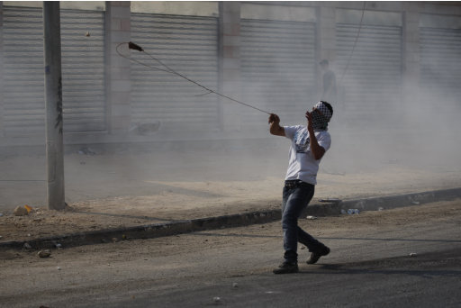 A Palestinian protester uses a slingshot to throw stones at Israeli soldiers, not seen, during clashes at the Qalandia checkpoint between the West Bank city of Ramallah and Jerusalem, Wednesday, Sept. 21, 2011. Palestinians clashed with Israeli security forces in Qalandia Wednesday, as thousands of flag-waving Palestinians rallied in towns across the West Bank to show support for their president's bid to win U.N. recognition of a Palestinian state. (AP Photo/Majdi Mohammed)