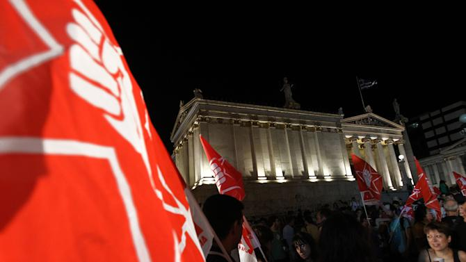 Supporters of Greece's radical left-wing Syriza party hold their party flags in front of Athens university, as they wait for head of the party Alexis Tsipras to speak, in Athens, late Sunday, June 17, 2012. Alexis Tsipras and his party shot to prominence in the May 6 vote, where he came a surprise second and quadrupled his support since the 2009 election. Syriza party has vowed to rip up Greece's bailout agreements and repeal the austerity measures, which have included deep spending cuts on everything from health care to education and infrastructure, as well as tax hikes and reductions of salaries and pensions.   (AP Photo/Petros Karadjias)