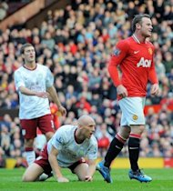 Manchester United's English forward Wayne Rooney (R) watches his shot as he scores his second goal during the English Premier League football match between Manchester United and Aston Villa at Old Trafford in Manchester. United won 4-0