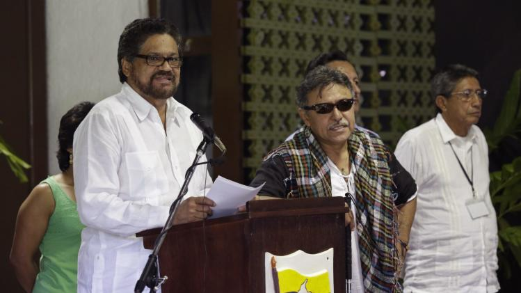 FARC lead negotiator Ivan Marquez reads from a document next to fellow negotiator Jesus Santrich during a conference in Havana