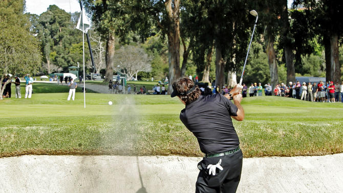 After his drive landed in the trees and his next shot went over the green into a bunker, Phil MIckelson hits to the green on his way to a triple bogey on the hole in the second round of the Northern Trust Open golf tournament at Riviera Country Club in the Pacific Palisades area of Los Angeles, Friday, Feb. 15, 2013. (AP Photo/Reed Saxon)