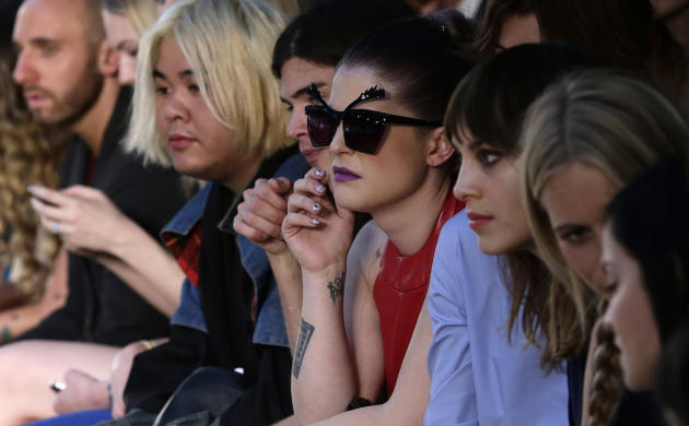 British TV personalitiy Kelly Osbourne, in sun glasses watches the House of Holland Spring/Summer 2013 presentation at London Fashion Week in London, Saturday, Sept. 15, 2012. (AP Photo/Alastair Grant