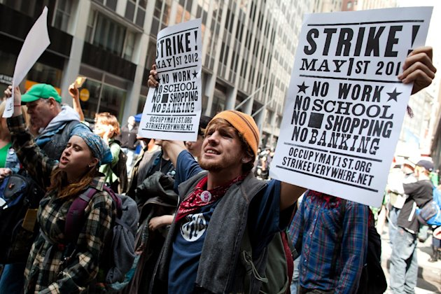 Occupy Wall Street demonstrators march while holding signs near Wall Street to celebrate the protest's sixth month, Saturday, March 17, 2012, in New York.  With the city's attention focused on the hug
