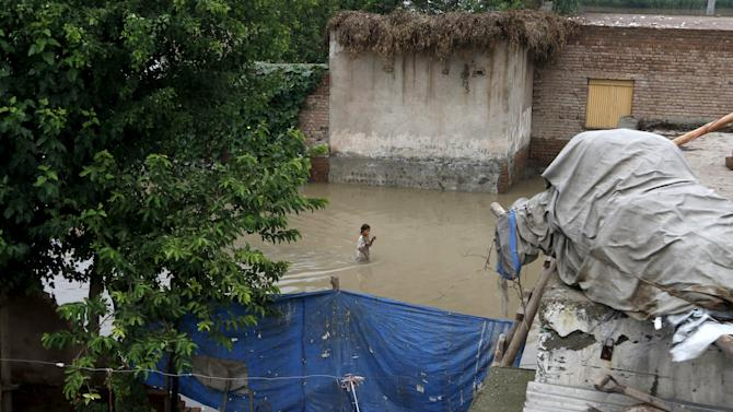 A girl walks through a flooded street at Camp Koruna area of Nowshera District, northwestern Pakistan