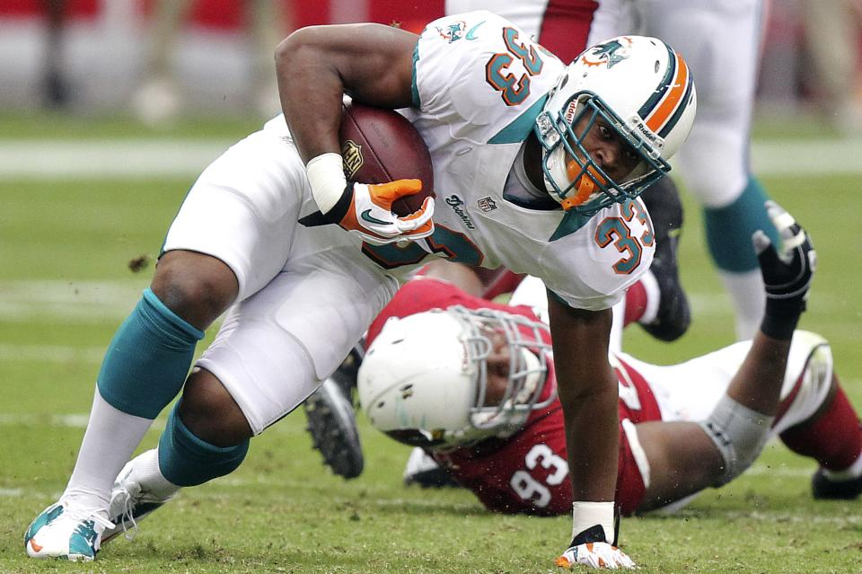 Miami Dolphins running back Daniel Thomas (33) is tripped up by Arizona Cardinals defensive end Calais Campbell during the first half of an NFL football game, Sunday, Sept. 30, 2012, in Glendale, Ariz. (AP Photo/Paul Connors)