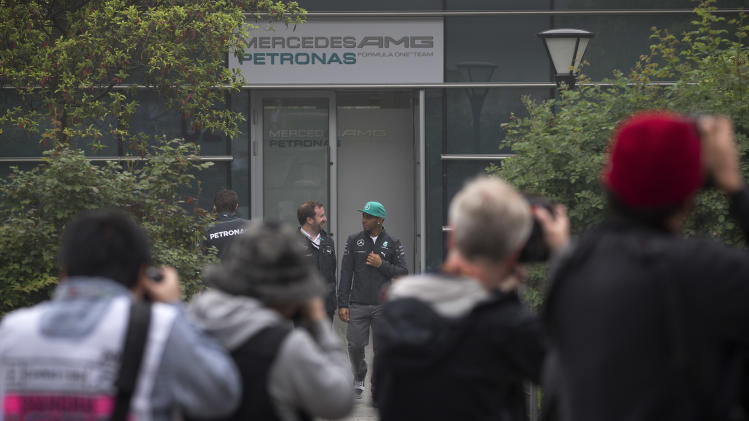 Photographers take pictures of Mercedes driver Lewis Hamilton of Britain, center right, and his crew walk to the paddock ahead of Sunday's Chinese Formula One Grand Prix at Shanghai International Circuit in Shanghai, China Thursday, April 17, 2014. (AP Photo/Andy Wong)