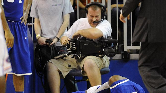 A cameraman grimmaces after a collision with Kentucky forward Nerlens Noel (3) during the second half of an NCAA college basketball game against Florida in Gainesville, Fla., Tuesday, Feb. 12, 2013. Noel injured his left knee and did not return. Florida won 69-52. (AP Photo/Phil Sandlin)