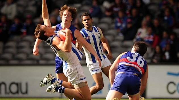 Drew Petrie of North Melbourne gets tackled by Liam Picken of the Western Bulldogs (AAP/AUSTRALIA ONLY)