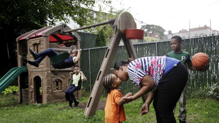 Olgita Blackwood kisses her son, Omarhie Blackwood, 1, in the yard for the Drew House in New York, Wednesday, Oct. 3, 2012.  The program, called Drew House, is one of a kind in the nation, where mothers arrested on felonies can live with their children, instead of in prison. The program has been lauded as a success that should be replicated around the country, but the small house is already full, and without additional funding and space, it can't grow.  (AP Photo/Seth Wenig)