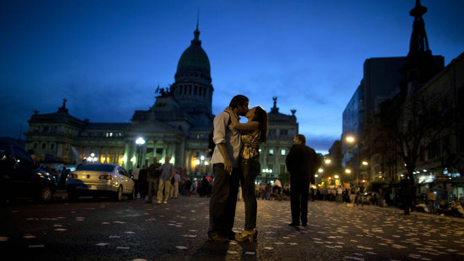 A couple kiss, outside the National Congress, during a protest against comprehensive judicial reform proposed by President Cristina Fernandez in Buenos Aires, Argentina, Wednesday, April 24, 2013. Lawmakers began debating major changes to the country's justice system Wednesday. Some of the changes would end indefinite injunctions against government actions, expand and popularly elect most of the magistrate's council and require executive, legislative and judicial authorities to publish their tax declarations online. (AP Photo/Natacha Pisarenko)