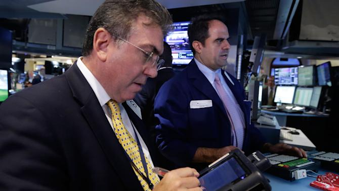 Trader John Bishop, left, works on the floor of the New York Stock Exchange Wednesday, Sept. 25, 2013. Investors continue to worry about the economy and the growing possibility of a government shutdown. (AP Photo/Richard Drew)
