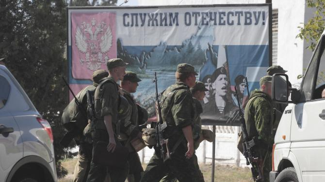 """Russian marines pass by a sign that reads """"Serving our country"""" in the Crimean port of Sevastopol"""